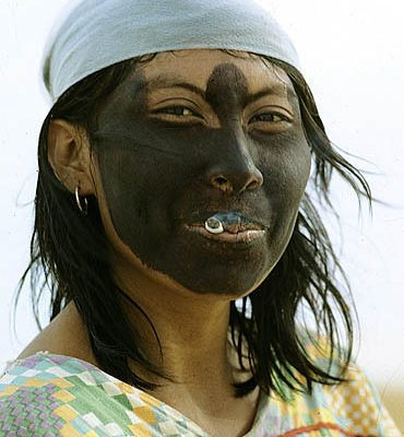 Colombia. Guajira Peninsula. Guajira Desert. Guajiro Indiian woman. She blackened her face with a powder extracted from a root to protect it against sunburn. She smokes her cigarette holding the lighted side inside her mouth.