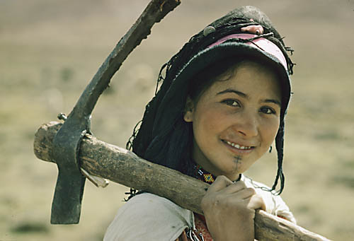 Morocco. High Atlas Mountains. Ait haddidu Berbe on her way to a moor, where she will unroot short bushes with her pick for the fire.